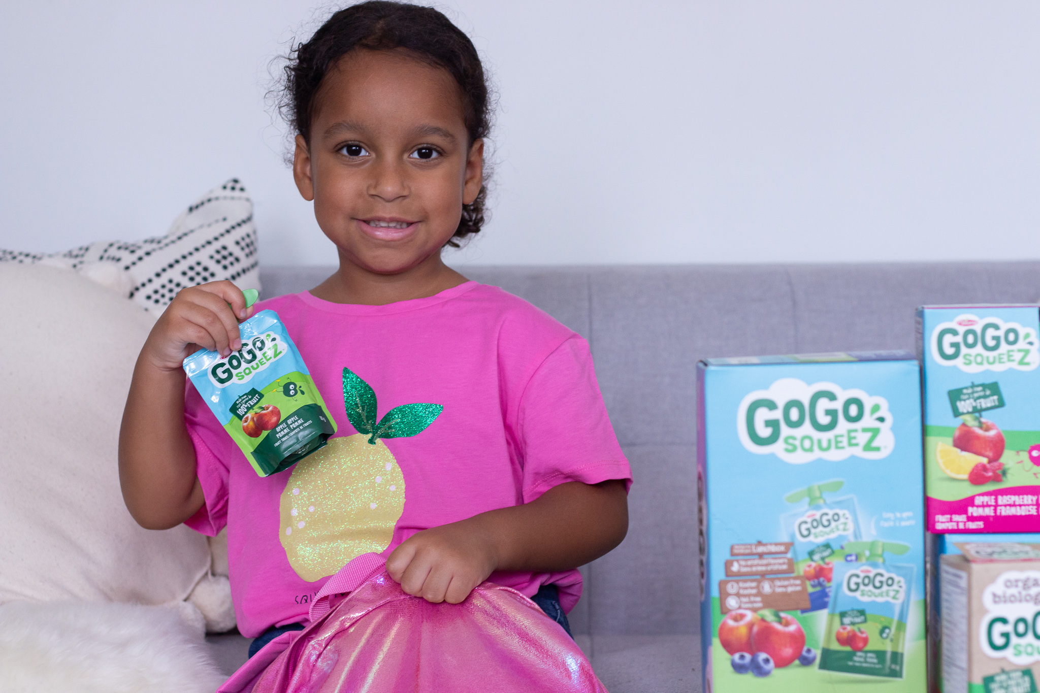 Little girl holding fruit sauce pouch