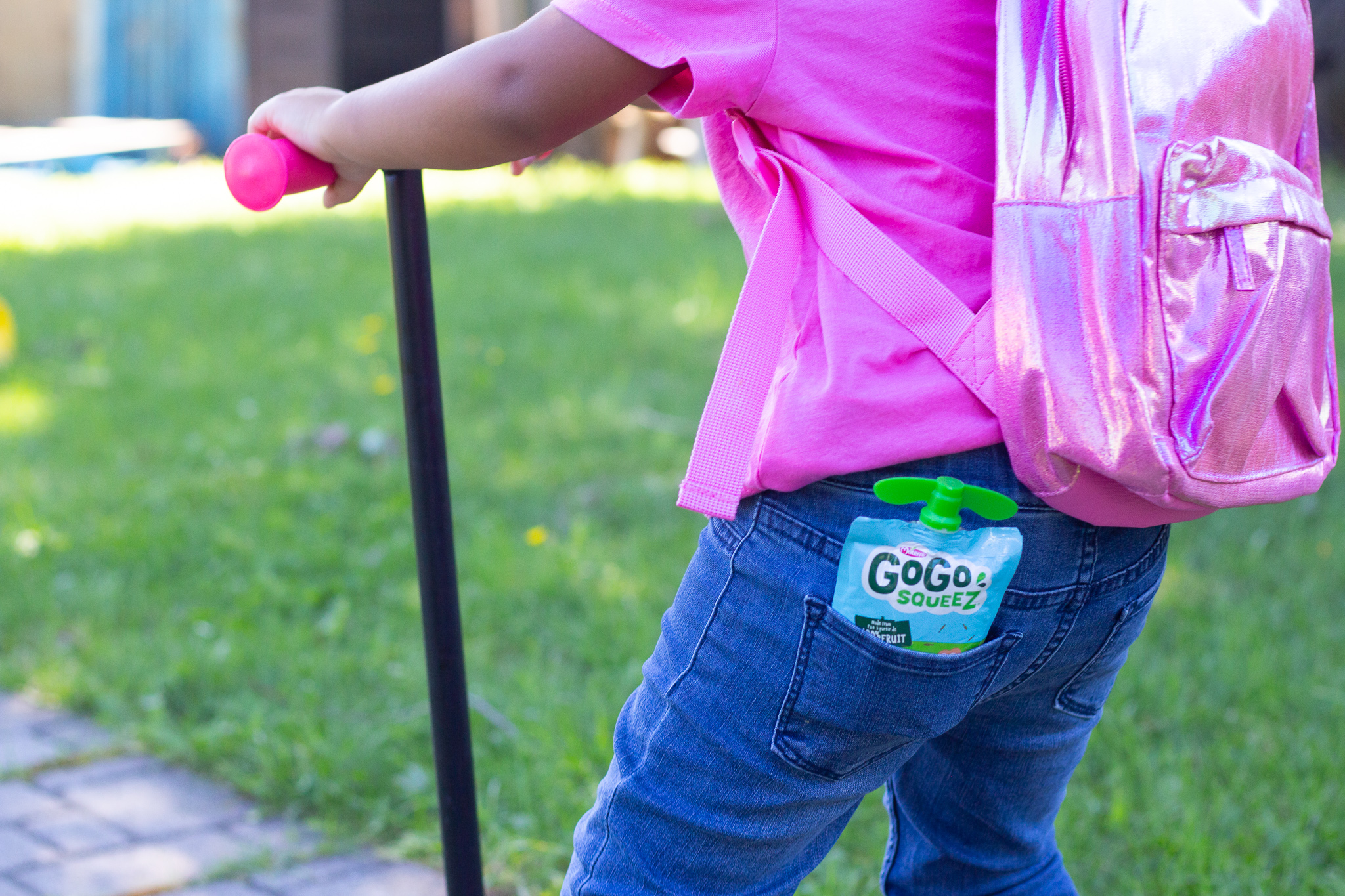 toddler with fruit pouch in her pocket