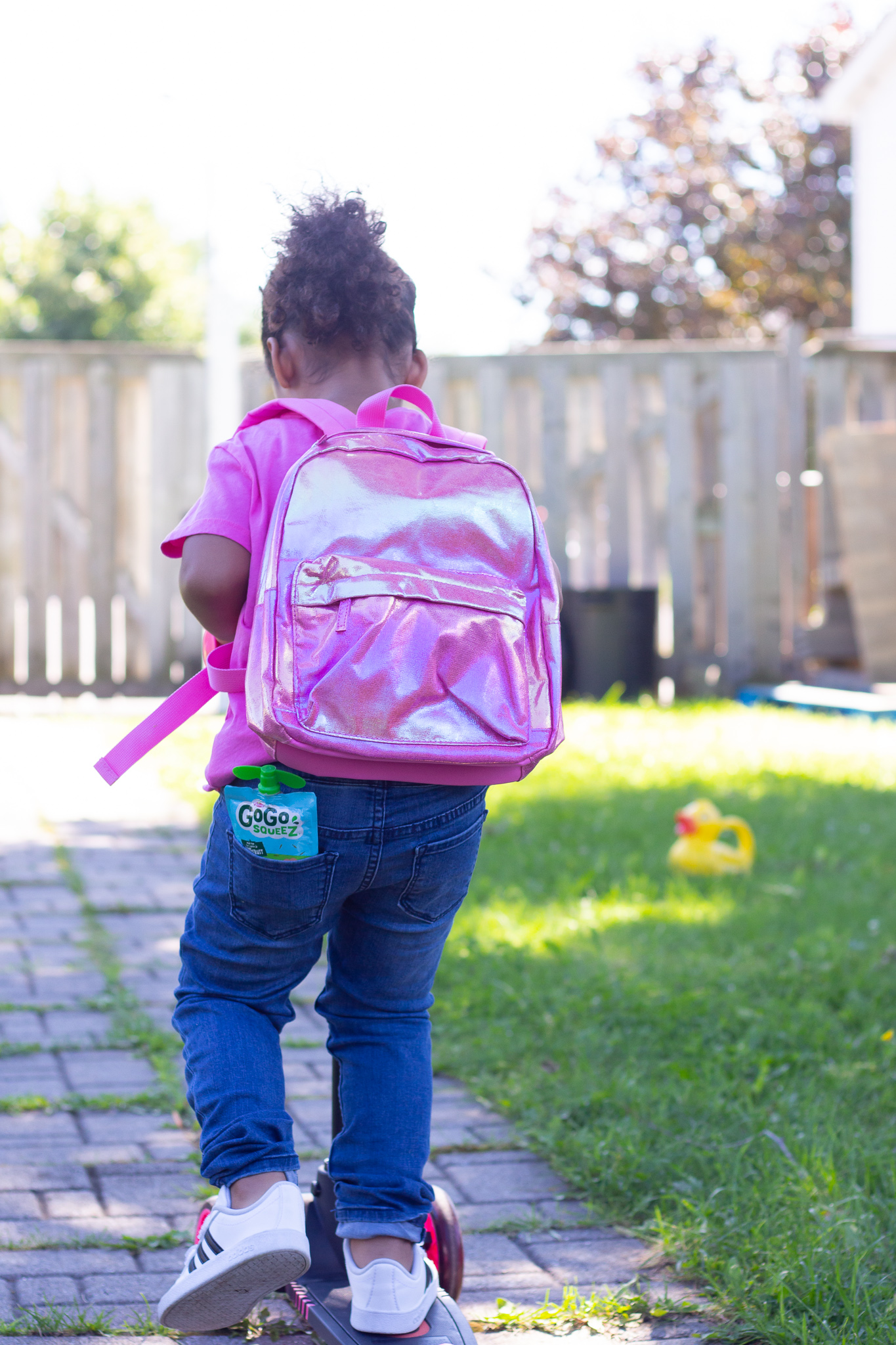 Toddler putting fruit pouch in backpack